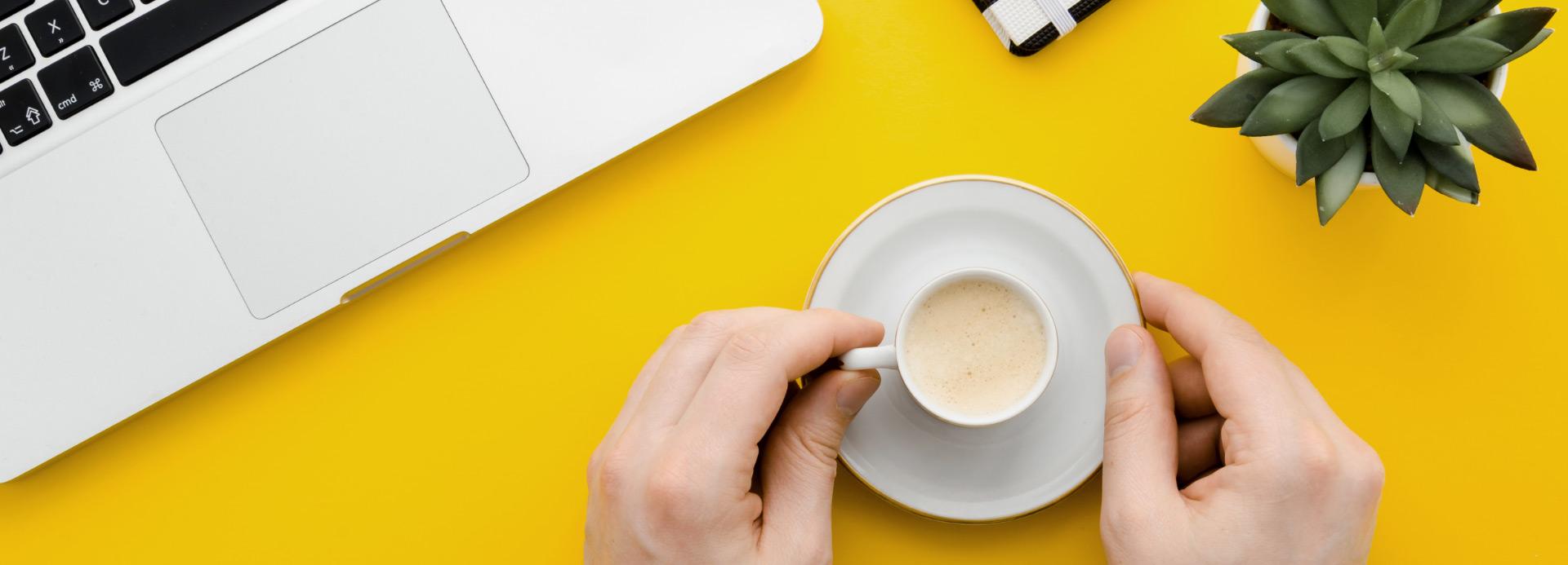 Bild Laptop und Kaffetasse auf gelben Untergrund